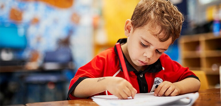 A Kindergarten student colouring in a worksheet.